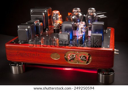 Vacuum tube stereo amplifier : Hi end power amplifier with wood chassis and carbon fiber plate in a black background - stock photo