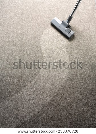 Vacuuming a carpet with a hoover - stock photo