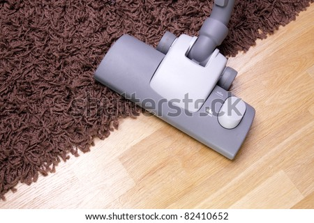 vacuuming the carpet in the house - stock photo