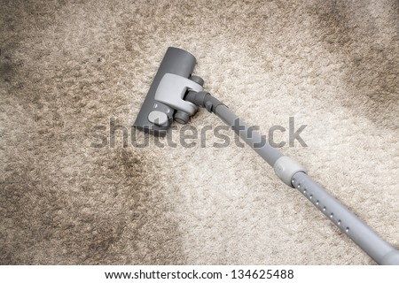 Vacuuming very dirty white carpet in home