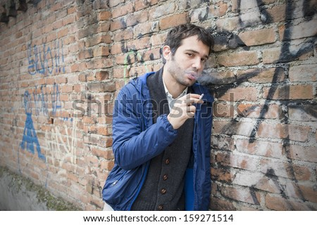 vagabond poor man in the street smoking cigarette - stock photo