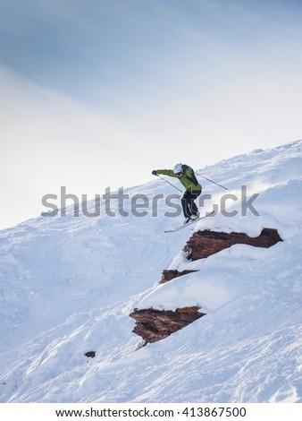VAIL, CO - JANUARY 2, 2016: Man skiing off rocky cliff jump on sunny day - stock photo