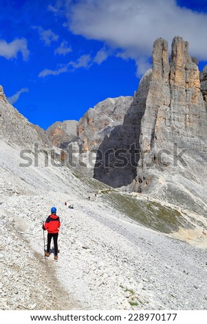 Vajolet towers and woman climber on rocky trail, Catinaccio massif, Dolomite Alps, Italy