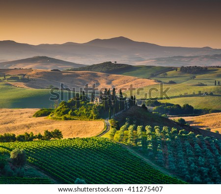 VAL D'ORCIA, ITALY - JULY 7 2014: Scenic Tuscany landscape with farmhouse amidst rolling hills and valleys in beautiful golden morning light at sunrise in summer on July 7, 2014, Val d'Orcia, Italy