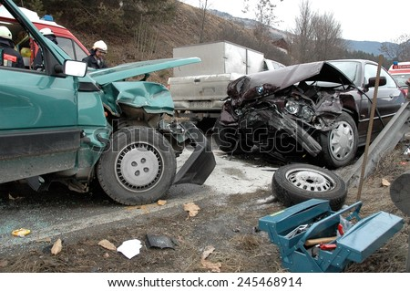 VAL GARDENA, ITALY - JANUARY 20, 2015: Fireman at work after frontal collision between two cars in winter time on the iced road. Destroyed car after opening with hydraulic clamps on January 20, 2015. - stock photo