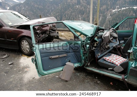 VAL GARDENA, ITALY - JANUARY 20, 2015: Fireman at work after frontal collision between two cars in winter time on the iced road. Destroyed car after opening with hydraulic clamps on January 20, 2015.