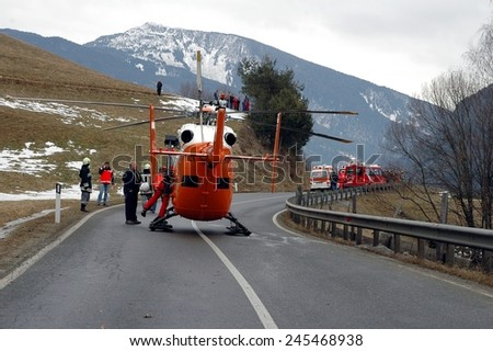 VAL GARDENA, ITALY - JANUARY 20, 2015: Helicopter ready to fly on the street to save and transport a seriously injured person to hospital after hard car accident on the iced road on January 20, 2015. - stock photo