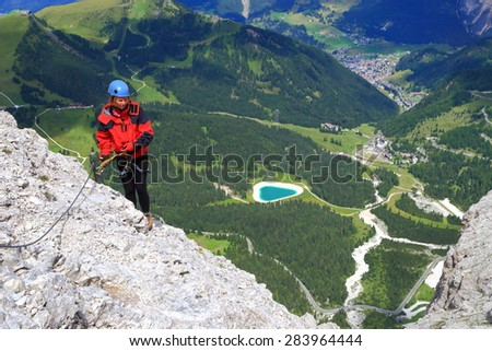 Val Gardena valley and climber ascending via ferrata route on Sella massif, Dolomite Alps, Italy - stock photo