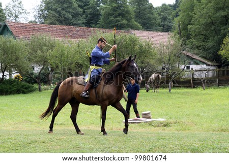 "VALCELE, ROMANIA - AUGUST 11: An unidentified Hungarian rider demonstrates archery on horseback at the yearly organized ""Maltezer camp"" on August 11, 2011 in Valcele, Romania."