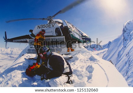 VALDEZ, ALASKA - APRIL 22: Snowboarder Esben Pedersen being dropped of by helicopter onf an isolated peak in the Chugach Mountains on April, 22, 2002. Valdez is the hub for Heli-skiing in Alaska. - stock photo