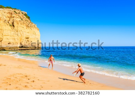 VALE CENTIANES BEACH, PORTUGAL - MAY 16, 2015: boy playing with his father on sandy beach in Algarve region, Portugal. - stock photo