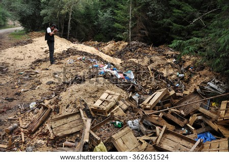 VALEA IERII, ROMANIA - SEPTEMBER 15, 2012: Sawdust and garbage dumped near a forest road in Valea Ierii. The rural areas of Romania are confronting the general problem of environmental pollution - stock photo