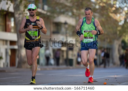 VALENCIA - NOVEMBER 17: Jose Seva (number 669) and Jesus Diaz (number 569) runners participate in Valencias marathon on November 17, 2013 in Valencia, Spain