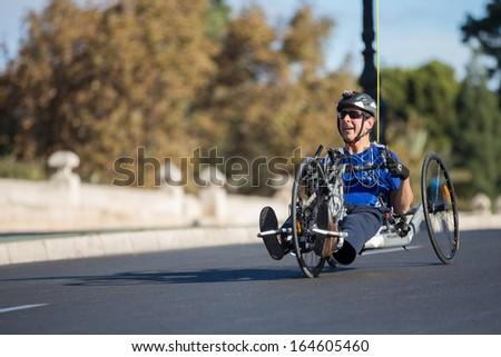 VALENCIA - NOVEMBER 17: Unidenfied hand-biker participates over his handicapped wheel chair in Valencias Marathon on November 17, 2013 in Valencia, Spain - stock photo