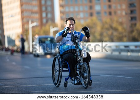 VALENCIA - NOVEMBER 17: Unidentified hand-biker participates over his handicapped wheel chair in Valencias Marathon on November 17, 2013 in Valencia, Spain - stock photo
