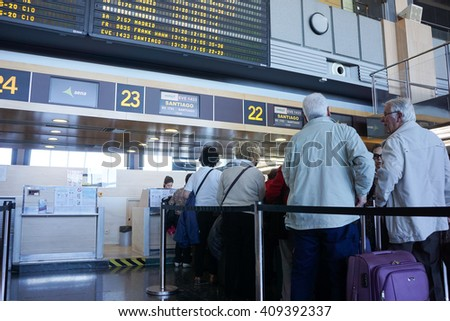 VALENCIA, SPAIN - APRIL 21, 2016: Airline passengers checking in at an airline counter inside the Valencia Airport. About 4.59 million passengers passed through the airport in 2015.