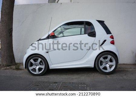 VALENCIA, SPAIN - AUGUST 20, 2014: A Smart Car parked in the street in Valencia, Spain.  The Smart Car is a small stylish city car with company headquarters in Germany, and the factory in France. - stock photo