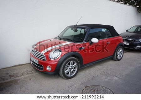 VALENCIA, SPAIN - AUGUST 20, 2014: Mini Cooper car parked in the street in Valencia, Spain.  In 1999 the Mini was voted the second most influential car of the 20th century, behind the Ford Model T. - stock photo