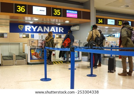 VALENCIA, SPAIN - FEBRUARY 14, 2015: Passengers at a Ryanair check-in counter at the Valencia airport. In 2014, Ryanair was the largest European airline by scheduled passengers carried. - stock photo