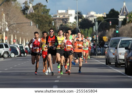 VALENCIA, SPAIN - FEBRUARY 22, 2015: Runners compete in the IV University of Valencia 5K run in the streets of Valencia. - stock photo