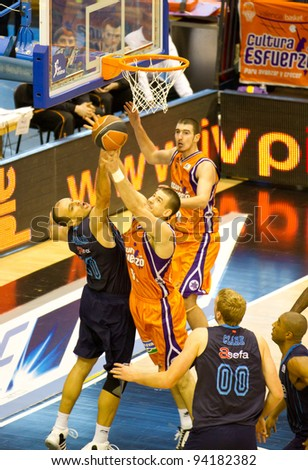 VALENCIA, SPAIN - JANUARY 28: Several players fighting under the basket during the ACB league match between Valencia Basket  and Asefa Estudiantes, 85-71, on January 28, 2012, in Valencia, Spain - stock photo