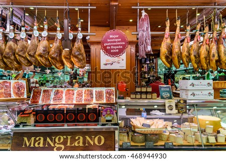 VALENCIA, SPAIN - JULY 20, 2016: Vendors Selling Ham, Bacon And Meat Products In Mercado Central (Mercat Central or Central Market), One Of The Largest Market Places In Valencia.
