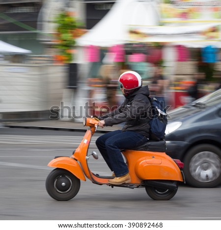 VALENCIA, SPAIN - MARCH 14, 2016: A man on a Vespa scooter traveling in the town center of Valencia with motion blur. Vespa is an Italian brand of scooter manufactured by Piaggio. - stock photo