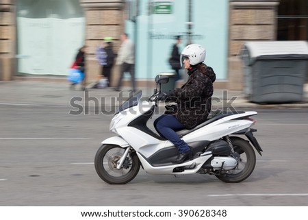 VALENCIA, SPAIN - MARCH 14, 2016: A woman riding a 2015 Honda PCX 150 scooter in the streets of Valencia. Originally developed in Thailand, the PCX is a popular commuter bike in Europe. - stock photo