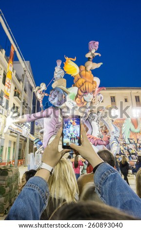 "VALENCIA, SPAIN - MARCH 15: Unidentified tourist takes photo with mobile phone of ""El Pilar"" falla ""Las Fallas"" (""the fires"" in Valencian) exhibition on march 15, 2015 in Valencia, Spain - stock photo"