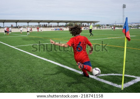 VALENCIA, SPAIN - SEPTEMBER 20, 2014: An unknown youth player taking a corner kick during a youth soccer match. Soccer is the most popular sport in Spain. - stock photo