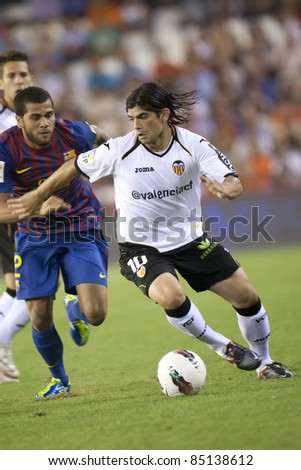 VALENCIA, SPAIN - SEPTEMBER 21:(R) Ever Banega with ball in the Spanish Soccer League between Valencia C.F. vs F.C. Barcelona - Mestalla Luis Casanova Stadium - Spain on September 21, 2011