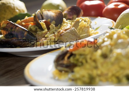 valenciana paella with some of its traditional ingredients or rather fish vegetable and meat - stock photo