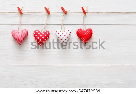 Valentine Background With Sewed Pillow Hearts Row Border On Red Clothespins At Rustic White Wood Planks