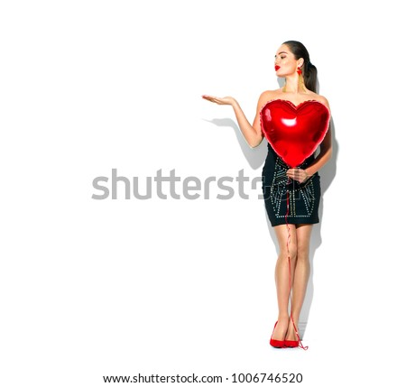 Valentine Beauty girl with red air balloon full length portrait pointing hand, isolated on background. Beautiful Happy Young woman presenting products. Holiday party, birthday. Joyful model