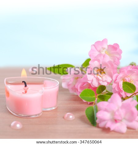 Valentine card of pink heart shaped candle, pearl beads and bouquet rose flowers on wooden and blue background, closeup