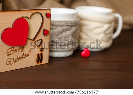 Valentine card with inscription Be My Valentine and hearts near cups of coffee with knitted cup holders and red heart on wooden background. Symbol of love. Valentine's day concept
