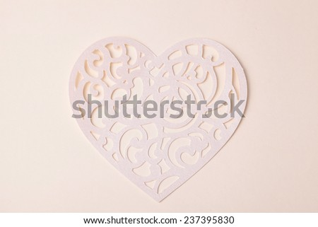 Valentine carving heart cutted from paper on the paper background - stock photo