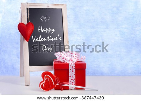 Valentine chalkboard, gift and heart shaped lollipop on white wood table and blue background, with Happy Valentines Day greeting.  - stock photo