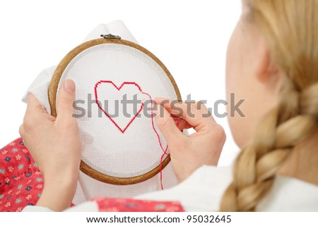 Valentine concept: girl with braids embroidering red heart