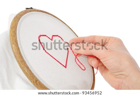 valentine concept: red heart being embroidered