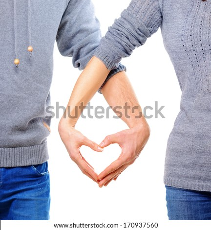 Valentine Couple in love showing Heart with their fingers. Love Concept. Valentines Day. Family with Heart made by their Hands. Young Man and Woman. Love Concept. Heart Sign. Valentines Day  - stock photo