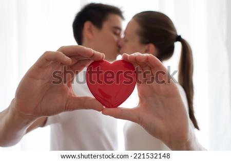 Valentine Couple. Portrait of kissing couple showing heart symbol. Happy Joyful Family. Love Concept. Valentines Day - stock photo