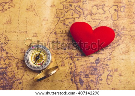Valentine day background. Old compass on vintage map with red heart. Retro filter. Direction to real love of your heart concept. - stock photo