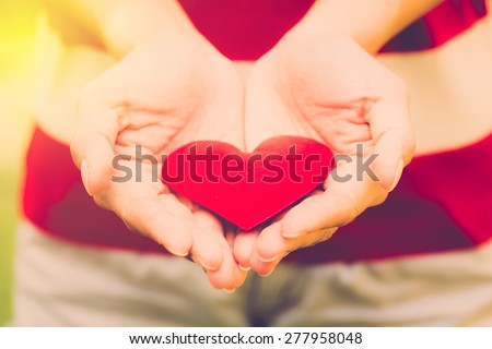 Valentine day background. Woman hold red love heart. Vintage filter. - stock photo
