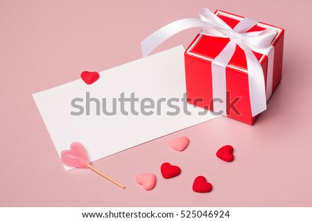Valentine day composition: red gift box with bow, stationery / photo template, candy and small hearts on light pink background.