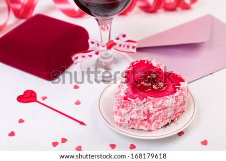 Valentine day still-life with cake, glass of wine, gift box and decorations - stock photo
