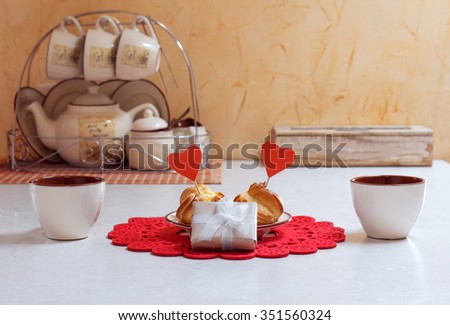 Valentine day tea or coffee. Table served with two cups, tasty eclairs decorated with hearts  and present gift box in vintage retro interior - stock photo