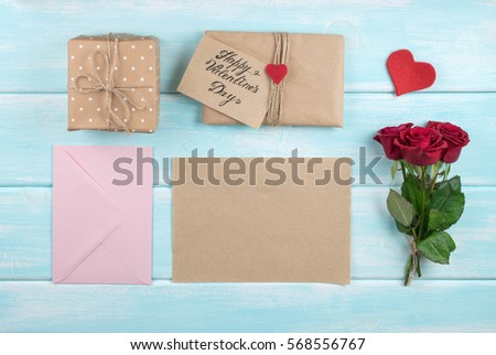 Valentine day theme. Top view of roses bouquet and eco paper with place for text. Packed gifts and envelope on shabby wooden table. Workplace for preparing handmade decorations.
