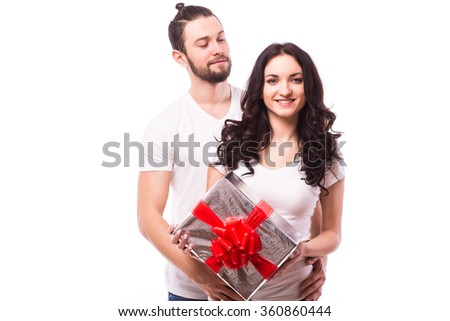 Valentine gift. Happy young couple with Valentine's Day present isolated on a white background. Happy man giving a gift to his girlfriend and look at she. Holiday - stock photo