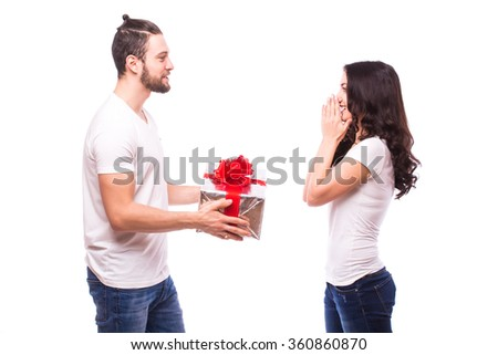Valentine gift. Happy young couple with Valentine's Day present isolated on a white background. Happy man giving a gift to his girlfriend.  She looks shocked at him. Holiday - stock photo